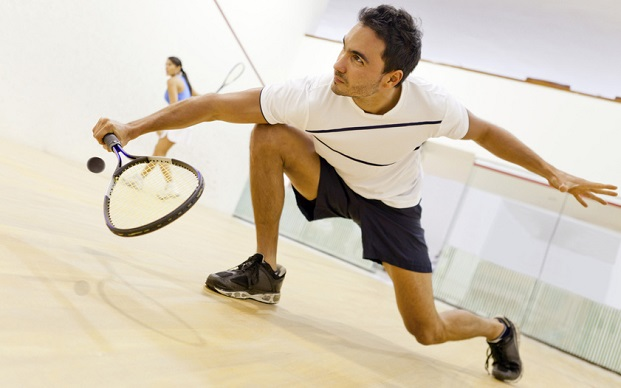 Hispanic couple playing squash